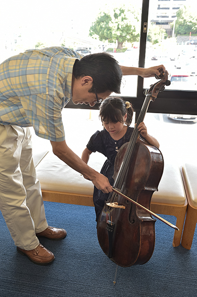 A child trying out an instrument at last year's concert. Performers patiently teach the children, even if it's their first time holding the instrument. (Photo: Shumpei Ohsugi)